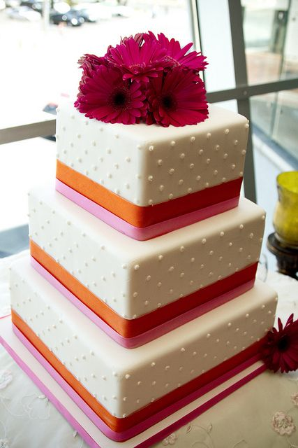 square wedding cake with gerberas.. green ribbons instead and the gerberas that are more orange