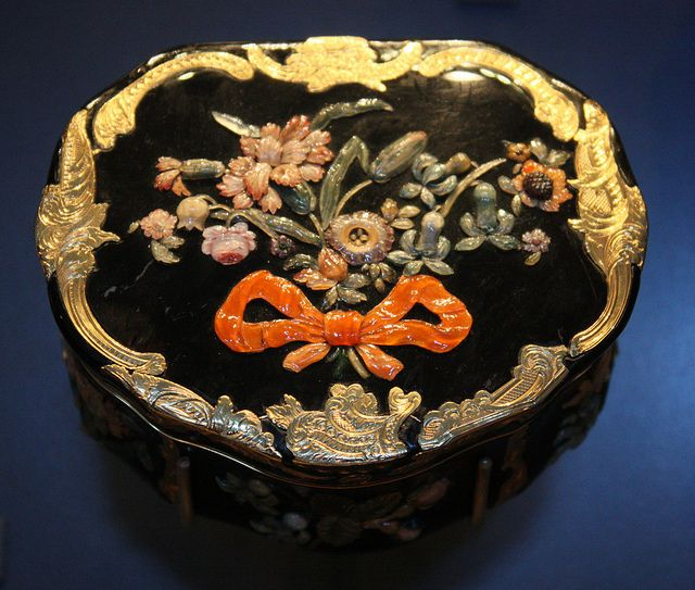 Snuffbox with flowers - V, 1765-75. This gold snuffbox is similar in shape and in the cutting of the hardstones to the jewelled boxes of Frederick the Great, King of Prussia (ruled 1740-86).    Berlin, Germany; maker's mark VB.  Chased gold and black marble inlaid with hardstones.
