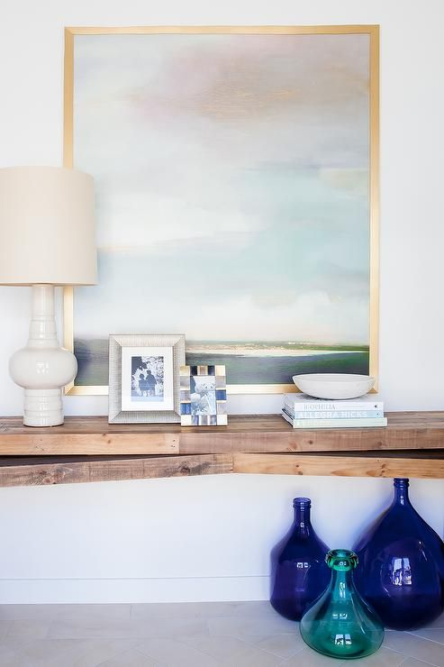 Chic foyer features a collection of indigo blue bottles and a green bottle tucked under a plank floating console table topped with an ivory lamp and art piece framed in a gold frame.