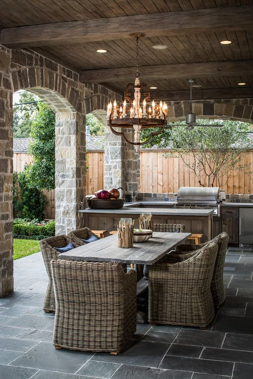 Outdoor kitchen and dining area, slate flooring under covered area with great lighting fixture/potlights, rustic stone aches/pillars