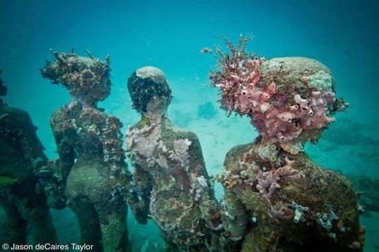 Life-size cement sculptures, submerged under water and left to become part of the underwater landscape. by angelica