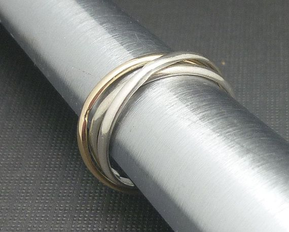 2 Sterling Silver rings are handmade and then intertwined with another 9 carat gold ring to form this ring. The individual rings and slide over