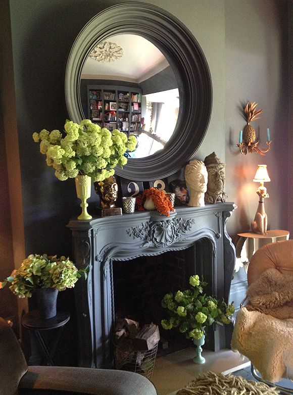 'Greying out' the fireplace and overmantel mirror. Removing the central table enables is to make a focal point of the fireplace. {credit:Abigail_Ahern}