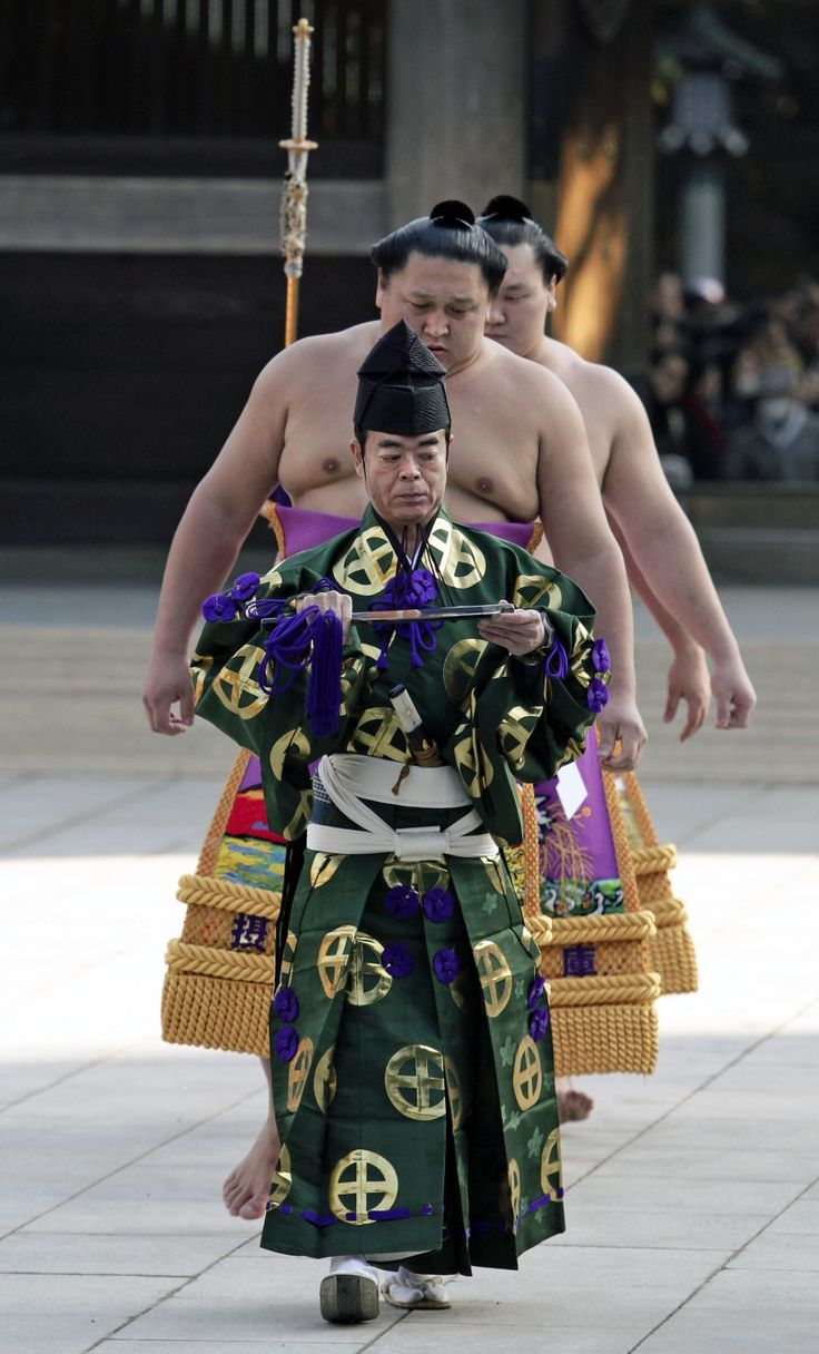 Sumo referee Shonosuke Kimura leads dew-sweeper (forerunner) Kyokutenho (C) and sumo grand champion Hakuho of Mongolia before Hakuho performs his ring entry forms to dedicate to the Meiji Shrine in Tokyo, Japan. (AP)