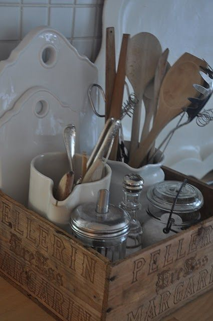 Pitchers, vintage jars and wooden spoons displayed in a vintage wooden box. Great way to organize and display your collections.
