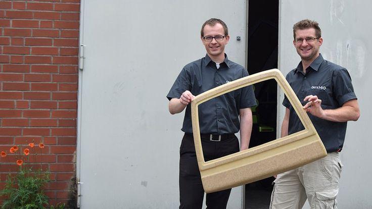 Zwei Männer stehen vor einer Wand und halten eine halbe Autotür in der Hand.