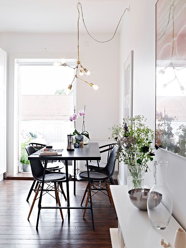 Attractive Eclectic Dining Room Design Featuring A Modern Brass Chandelier, Wood Table,  Eames And Wishbone Style Chairs, Large Framed Poster Artwork And A White ...