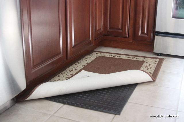 Industrial $17 anti-fatigue mat from Home Depot UNDER a nice rug in the kitchen.