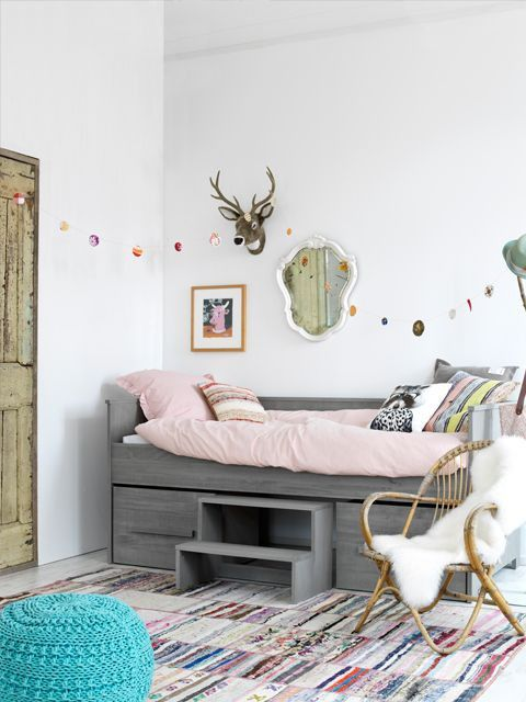 A simple grey bed, with some small additions to the wall make it so stylish and simple. We love that rug and the mix of wood and colour together.