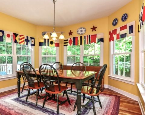 Nautical Decorating with Classic American Charm. In the dining room signal flags are used as valance.