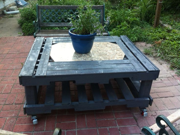 Back patio table made with 3 used pallets and scrap granite piece. Only monetary costs was added wheels and paint.