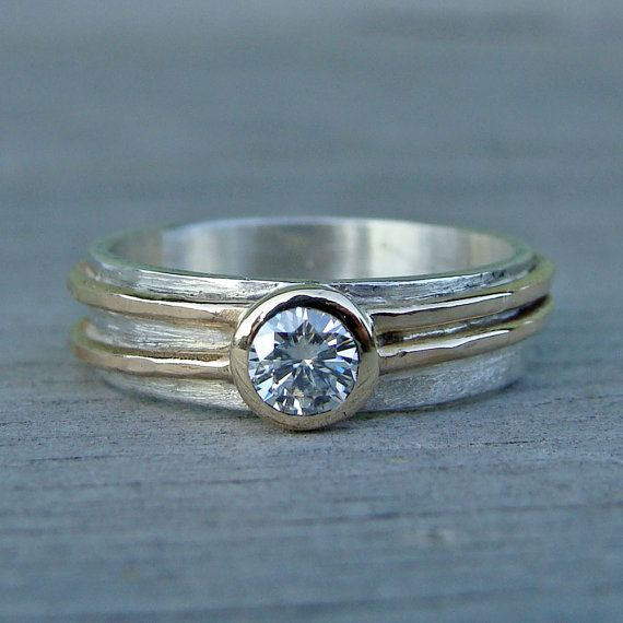 A beautiful 4mm moissanite sits in a 14k gold bezel on a 5mm wide layered 14k yellow gold and sterling silver band. This is a design that can work really well as a wedding ring, or for any other occasion. It has a very low bezel, which makes it very comfortable and easy to wear. All of the metal used in this piece is from recycled sources. This is truly a piece you can feel good about wearing, knowing that its creation did not exploit workers or harm the environment. Please allow three to…