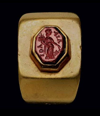 A ROMAN GOLD AND RED JASPER FINGER RING CIRCA 1ST CENTURY A.D. The plain wide hoop carinated at the shoulder, with an octagonal bezel set with a flat octagonal jasper, engraved with the goddess Fortuna facing right, wearing a tunic and mantle, holding a ship's rudder in her left hand, a cornucopia in her right, a modius surmounting her head, standing on a short groundline  | Christie's