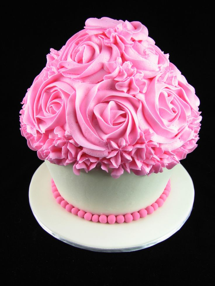 Giant vanilla cupcake with electric pink buttercream and fondant pearls.