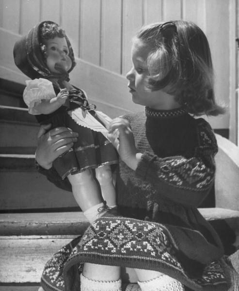 Walter Sanders, A little girl sitting on the steps with her doll, Germany, May 1949.