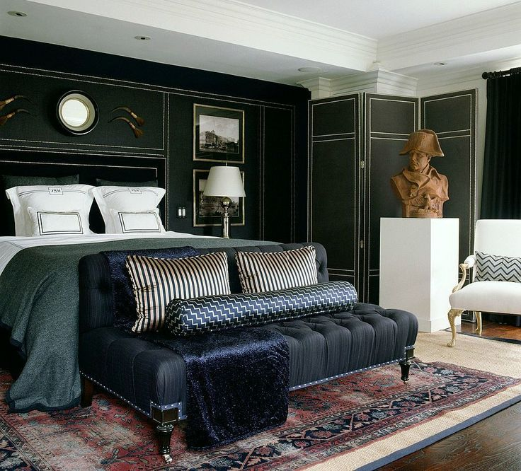 Mary McDonald sexy dar bedroom, that folding screen, the panel divisions marked out with nail heads, the mirror over the bed, merlot and navy traditional rug layered over a  large black or navy bordered sisal or grass rug