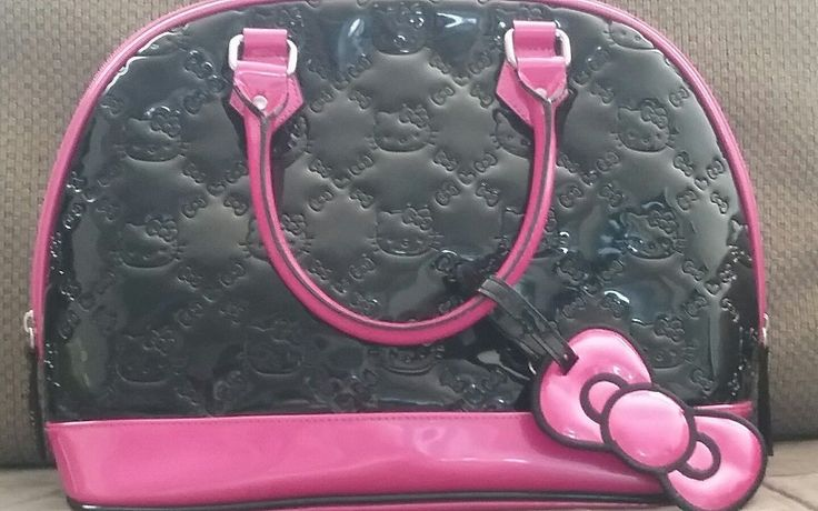 black Hello Kitty handbag with hot pink trim. this bag is in very good shape all blemishes have been included in pictures. zipper is working keychains and zipper pulls are all intact. there's plenty of space inside several Pockets to put your t...