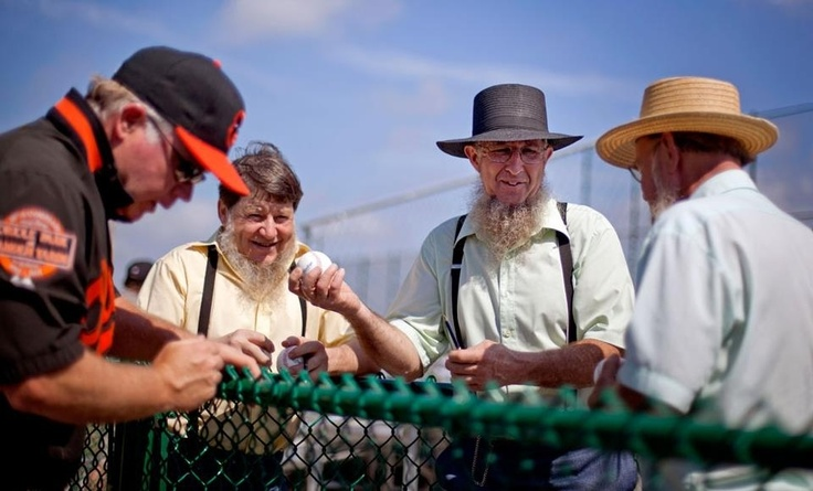 Baltimore Orioles manager Buck Showalter signs a few baseballs for three Amish men at Orioles Spring Training in Sarasota, Florida. Early contender for best Spring Training photo this year.
