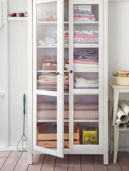 Ikea Smadal bookcase with glass doors... line the back with pretty paper. Love it.