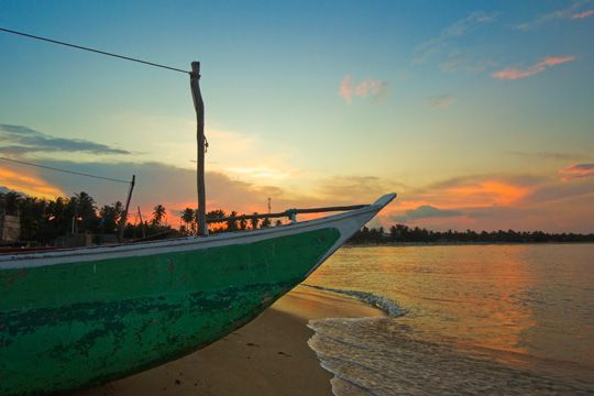 Outrigger boat at sunset at this fishing beach and popular tourist surf destination, Arugam Bay, Eastern Province, Sri Lanka