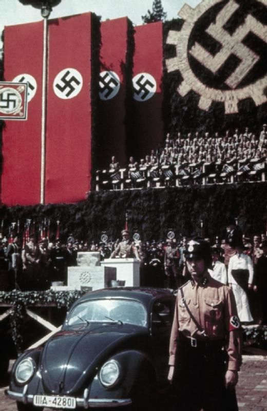 Adolf Hitler makes a speech during a cornerstone-laying ceremony to mark the start of construction of the Volkswagen factory at Fallersleben, June 1938. In the foreground is the prototype Volkswagen car designed by Prof Dr F Porsche and handmade by the Mercedes Benz car factory.