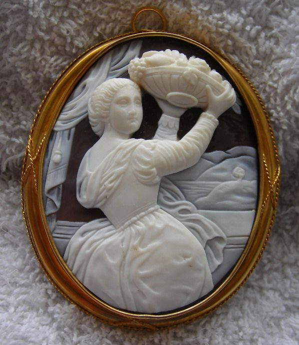 Circa 1860 Italian Sardony Shell, 18K gold cameo depicting the subject Girl with a Basket of Fruits, after a painting by Titian.