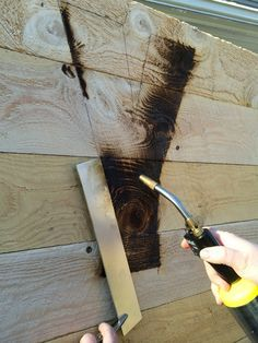 Burn letters on wooden pallet using a torch and metal straight edge. OLT