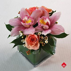 Cymbidium orchids and roses arrangement in a glass cube