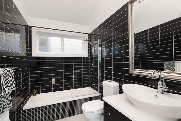 Immaculate home, spacious designer interiors, sleek main bathroom, shower above bath, black tiles, Pilcher Residential