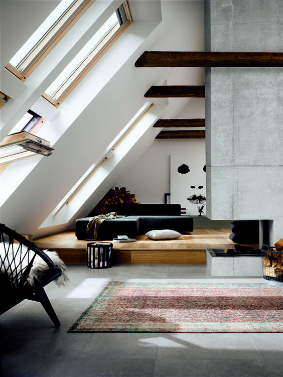 modern attic lviing room with a concrete fireplace
