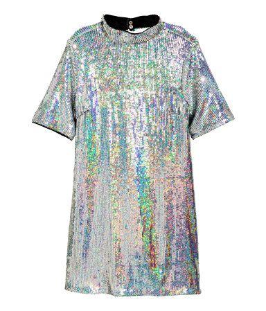 Zilverkleurig. Een korte, rechte jurk van mesh met paillettenborduursel. De jurk heeft korte mouwen, een halsboordje, een diep uitgesneden rugdecolleté en