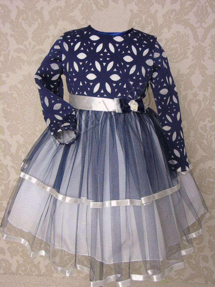 Niezwykła sukienka z dzianiny w kwiaty z granatowym podwójnym tiulem obszytym jasną lamówką. Odszyta płótnem bawełnianym oraz podszewka. Sukienka posiada długi rękaw oraz kryty zamek. Atłasowa szarfa w pasie, wiązana z tyłu kreacji umożliwia dopasowanie sukienki do ciała.