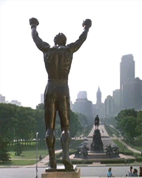 "rocky statue -The 72 stone steps before the entrance of the Philadelphia Museum of Art in Philadelphia, Pennsylvania have become known as the ""Rocky Steps"" as a result of their appearance in the triple-Oscar-winning film Rocky and four of its sequels, Rocky II, III, V and Rocky Balboa, in which the eponymous character runs up the steps to the song ""Gonna Fly Now"". Tourists often mimic Rocky's famous climb, a metaphor for an underdog or an everyman rising to a challenge."