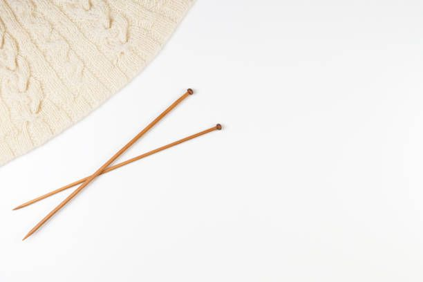 knitting and pair of wooden knitting needles on white background