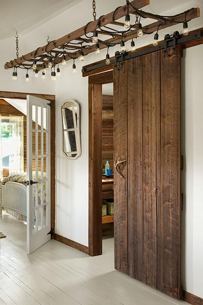 entrance to the master bathroom with a salvaged wood sliding barn door and an old ladder draped with exposed lightbulb string lights as a light fixture