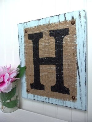 Burlap laid on distressed wood with studs, printed letter on top, cute.