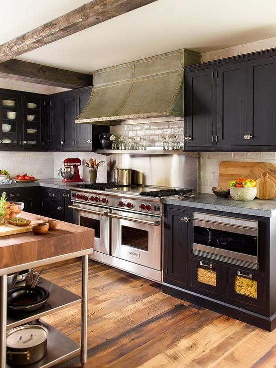 Stunning well appointed kitchen features a wood and stainless steel freestanding island positioned on a rustic wood floor facing a dual Wolf range fitted with a stainless steel cooktop shelf mounted beneath a matte metal studded hood flanked by black shaker cabinets finished with vintage latch hood hardware.