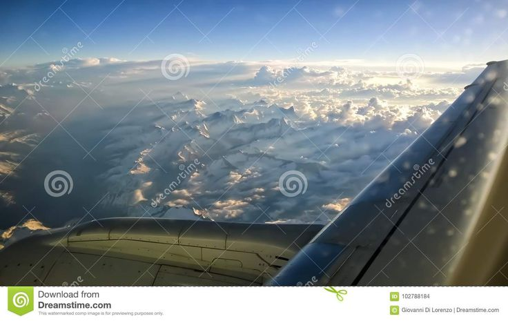 View From Airplane Window Of Mountains With Snow On The Top, Clouds, Wing And Blue Sky. For Travel Concept - Download From Over 67 Million High Quality Stock Photos, Images, Vectors. Sign up for FREE today. Image: 102788184