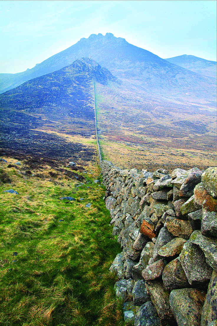 The Great Wall of – County Down? The Mourne Mountains are crisscrossed by endless, weaving dry-stone walls, like a patchwork stitch that stretches across the length and breadth of this island. Many were built during famine times; still more were built by farmers clearing land by digging stones from the soil itself, then expertly stacking them to divide land, protect livestock, and impose a semblance of order on the wild landscape of Ireland.