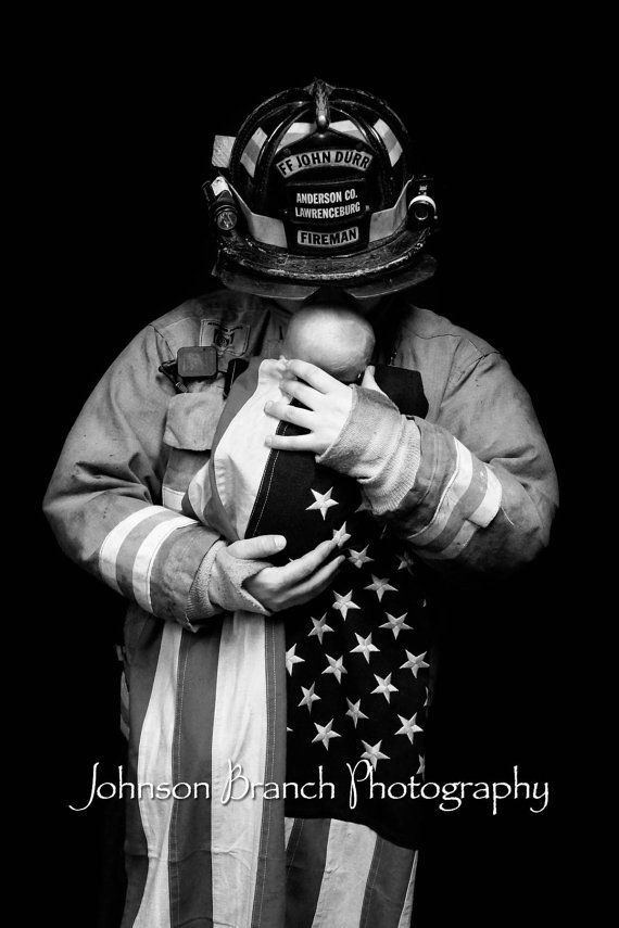 Firefighter holding baby wrapped in American flag, black and white photo. Father and son fireman photo  Johnson Branch Photography