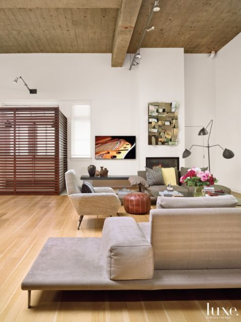 Sofas by Roche Bobois and a vintage Italian armchair—from Raritet Antique Gallery in Austin—covered in a Pollack fabric gather in the expansive living area. The three-arm Serge Mouille floor lamp is from Design Within Reach, and the midcentury Cubist mirror is from Classic Modern Design through 1stdibs.