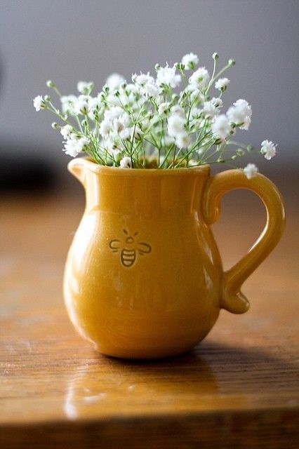 Honeybee on a ocher pitcher with small white spring flowers. Sweetness in its simplicity.