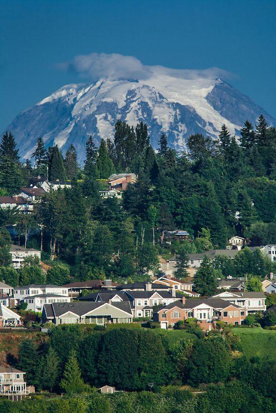 A snow caped Mt. Rainier towers over the suburbs of Tacoma, Washington