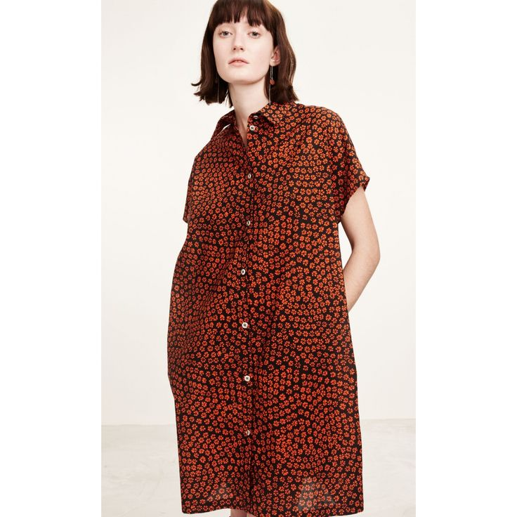 A loose fit button-up dress in a blue and red Ajusko pattern. Made of light cotton, this dress has short sleeves, pockets at the side seams and an above-knee hemline.