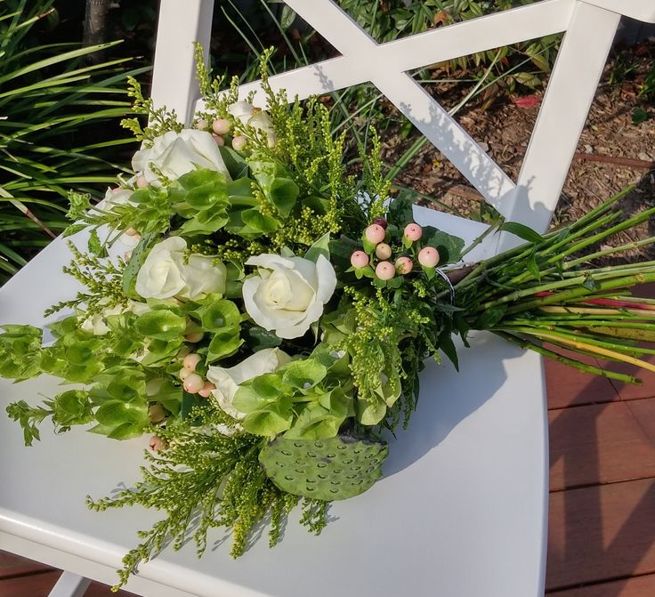 HAND TIED BOUQUET featuring roses, lotus pods, bells of Ireland, soldiago and hypericum.