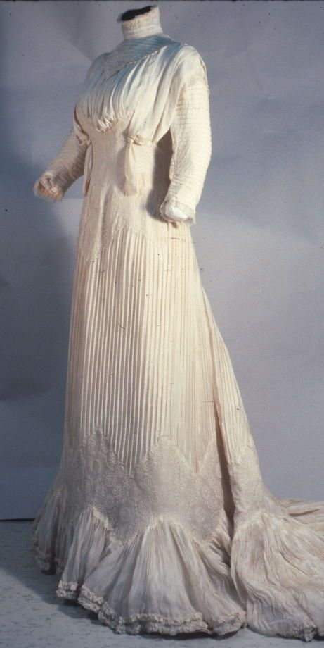 Woman's wedding dress Date: 1901 Media: Silk Crepe De Chine, Taffeta, Maline, And Satin Country: United States Accession Number: 45.36.6a One-piece crepe de chine dress with 3/4 length sleeves and high neck, finely tucked skirt above wide zigzag insertion of embroidered silk and chiffon flounce