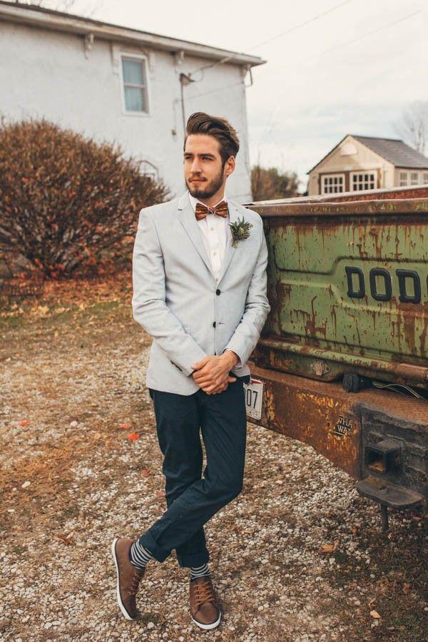 Alternatief geklede bruidegom in spijkerbroek, licht jasje en wit overhemd met trendy dasstrik.