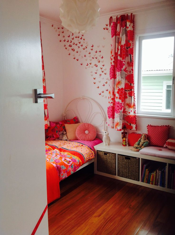 Sleeping corner with a wall of butterflies in soft orange, red, and pinks. Vintage iron bed... Homemade cushions and curtains. Lots of cushions in the reading corner