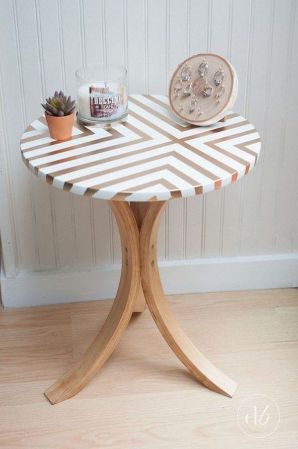 Takes an old Ikea table and gives it a gorgeous and trendy side table makeover using some tape, gold spray paint, and wood stain.