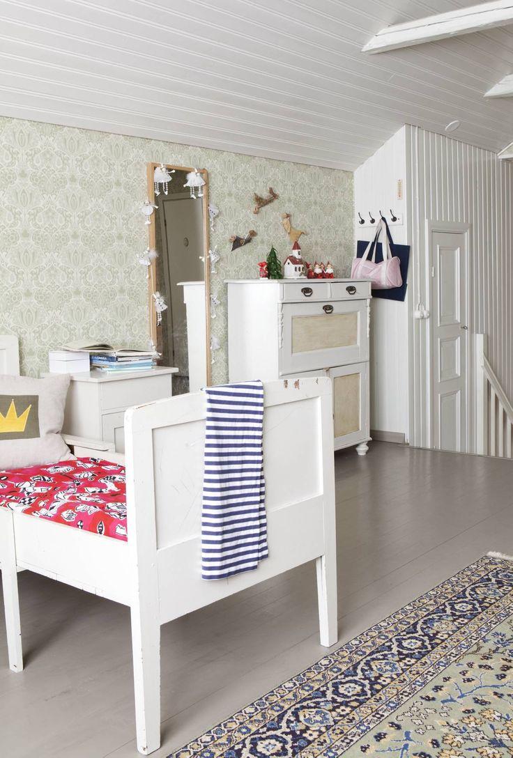 Tyttöjen huoneen kattohirret otettiin remontissa esille ja maalattiin valkoisiksi. Portaista on käynti vaatekomeroon. Valkoinen lipasto on hankittu kirpputorilta.